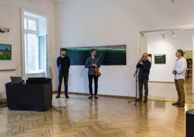 Z lewej strony mężczyzna ubrany na czarno, po środku mężczyzna trzymający skrzypce, po prawej mężczyzna mówiący do mikrofonu. W tle obraz wiszący na białej ścianie.