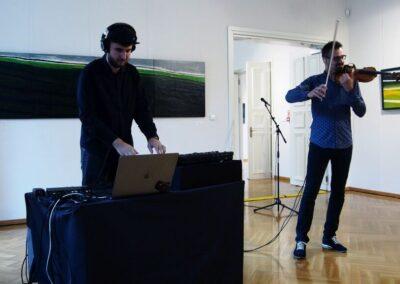 Z lewej mąarno gra na instumencie elektronicznym, po prawej mężczyzna grający na skrzypcach.żczyzna ubrany na cz