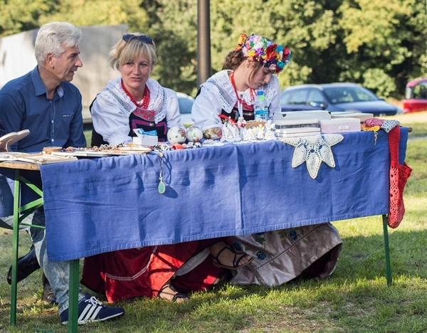 Mężczyzna w niebieskiej koszuli oraz dwie kobiety w tradycyjnych śląskich strojach siedzą przy stole nakrytym niebieskim obrusem. Na stole rękodzieło - serwetki itp.