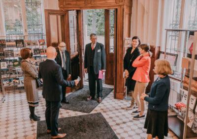 Hrabia Hans Ulrich Schaffgotsch stojący w wejściu do pałacu, witany przez dyrektora i pracowników centrum.