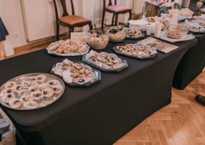Stół nakryty czarnym obrusem.Na stole patery z ciastkami i przekąskami.