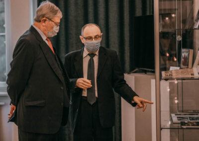 Dr Kuzio-Podrucki pokazujący Hrabiemu książki w gablocie.