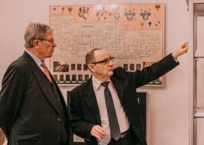 Dr Kuzio-Podrucki pokazuje hrabiemu eksponaty w gablocie, w tle plansza z drzewem genealogicznym.