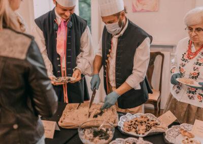 Dwóch mężczyzn w śląskich strojach i czapkach kucharskich kroi prosiaka z ciasta ziemniaczanego. kobieta ws troju sląskim trzyma talerzyk z porcją dania.