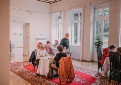 Ludzie siedzący przy stolikach w sali rozetowej, rozmawiajacy i jedzący poczęstunek. na podłodze dywan.