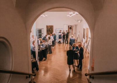 Ludzie zebrani na Pałacowych smakach w sali kolumnowej - widok ze schodów.