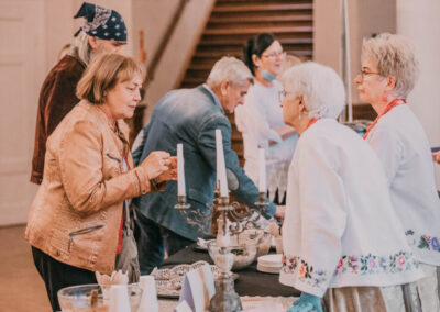 Z lewej strony stołu ludzie częstujący sie potrawami. Z prawej panie w tradycyjnych strojachśląskich podające dania.