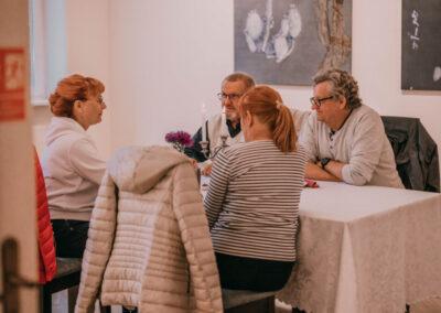 grupka ludzi siędzących przy stole nakrytym białym obrusem. na stole swiecznik i zapalone świece, kwiaty. ludzie rozmawiaja.