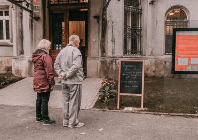Dwoje starszych ludzi przed wejściem do pałacu czytaja napis na tablicy: Zapraszamy na Pałacowe Smaki.