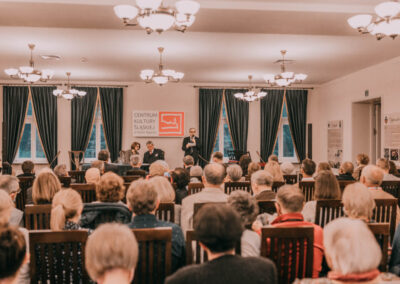 Dr Kuzio-podrucki mówiący do mikrofonu. Obok przy stole siedzi hrabia i tłumaczka. Na sali widać zgromadzonych gości.