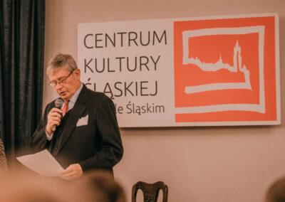 Hrabia Schaffgotsch czytajacy przemówniene. W tle logo Centrum kultury Śląskiej w Nakle Śląskim.