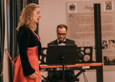 Agnieszka Wiśniewska-Rak w czerwonej sukni śpiewająca na scenie. Obok na pianinie graz mężczyzna w okularach (Mateusz Meisner).