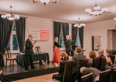 Na scenie dyrektor Centrum wręcza kwiaty pani Wiśniewskiej_rak. Z prawej pianista pan Meisner, z lewej dr Arkadiusz Kuzio-Podrucki