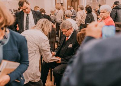 Hrabia podpisujący książke. kobieta wskazująca na książkę. W koło zebrani ludzie.