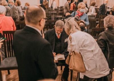 Hrabia podpisujący książkę. Obok pochylona kobieta, w koło ludzie zgromadzenia na spotkaniu.