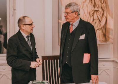 Dr Kuzio-Podrucki z lewej rozmawia z hrabia Schaffgotschem (z prawej). W tle obraz Marty Czarneckiej-Tokarz.