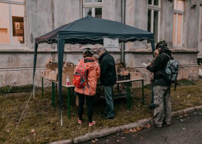 Namiot nr 3 posiłek regeneracyjny. Stoliki z kartonami. Dwóch pracowników wydaje posiłek dwóm osobom.
