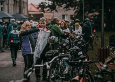 Kobieta oglądająca rajdowa koszulkę, obok mężczyzna. Stoją przy zaparkowanych wzdłuż alejki rowerów. W tle przechodzący ludzie.