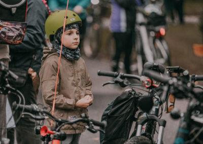 Chłopiec w zielonym kasku stoi przy rowerze, W koło widac inne rowery i przechodzących ludzi.