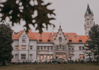 Tył pałacu w Nakle Śląskim a przy nim namioty i dużo ludzi z rowerami.