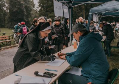 Siostra zakonna podpisujaca sie na liście startowej. Przed nia siedzi pracownik rejestrujący uczestników.