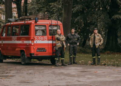 Trzech strażaków przy małym wozie strażackim.