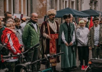 Kobieta i mężczyzna z bractwa kurkowego w strojach szlacheckich w otoczeniu innych ludzi przed pałacem.