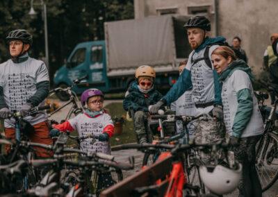 Kobieta i mężczyzna z dójką dzieci na rowerach. Z lewej inny mężczyzna na rowerze, z prawej siostra zakonna. W tle dostawczy samochód.