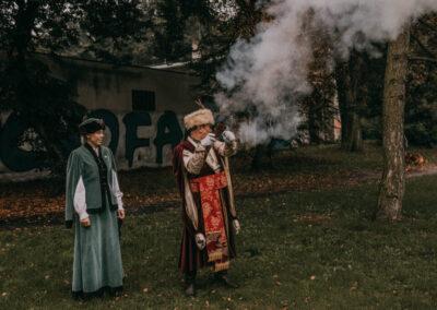 Kobieta i mężczyzna z bractwa kurkowego w strojach szlacheckich. Mężczyzna strzela. Wokół niego unosi się dym.