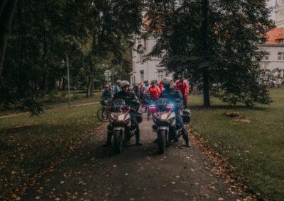 Z przodu dwa motocykle policyjne, za nimi peleton rowerzystów. W tle pałac w Nakle Śląskim.