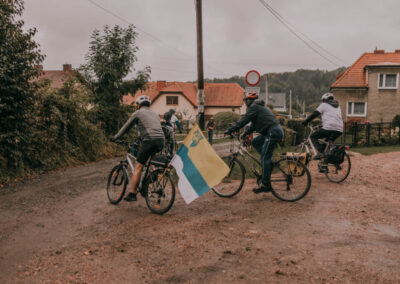 trzech rowerzystów na zakręcie, jeden ma z tyłu flagę powiatu tarnogórskiego.