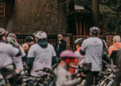 Arkadiusz Kuzio-Podrucki przemawia przez mikrofon do rowerzystów pod restauracją Pod Dębem.
