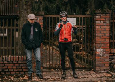 Dyrektor w kasku i ciemnych okularach mówi do mikrofonu. obok stoi Arkadiusz Kuzio-Podrucki. Za nimi ogrodzenie z cegły i metalu.