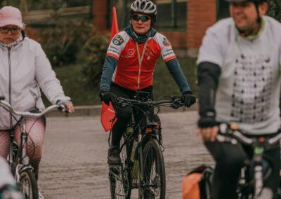 Dyrektor centrum i dwóch rowerzystów: z lewej kobieta w czapce z daszkiem, z prawej męższyzna, jadą wybrukowaną drogą.