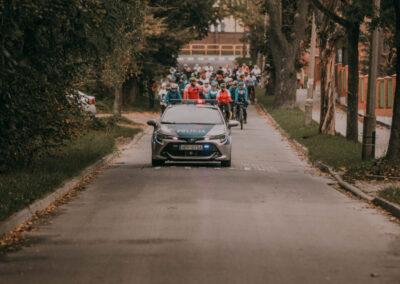 policyjny radiowóz a za nim peleton rowerzystów.