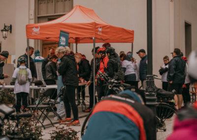 grupa ludzi w kolejce po ciepłe napoje pod pomarańczowym namiotem z napisem Becek.