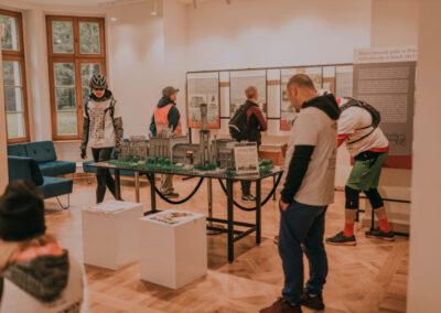 Uczestnicy rajdu w sali wystawowej w pałacu Tiele-Wincklerów oglądaja rekonstrukcję pałacu z klocków lego.