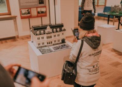 Kobieta robiąca zdjęcie telefonem komórkowym rekonstrukcji pałacu z klocków lego.