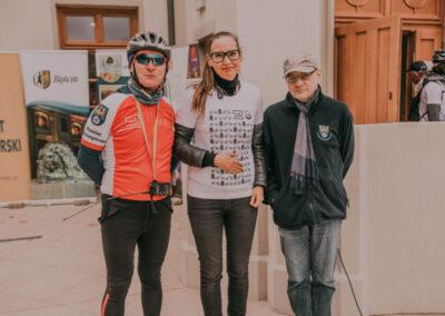 Z prawej dyrektor centrum w kasku i ciemnych okularach, po srodku dyrektor pałacu w Miechjowicach, z prawej dr Arkadiusz Kuzio-Podrucki. W tle fasada pałacu w Miechowicach i banery sponsorów rajdu.