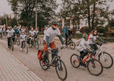 Grupa rowezrystów dorosłych i dzieci w koszulkach rajdowych na tle budynku szkoły w Miechowicach.