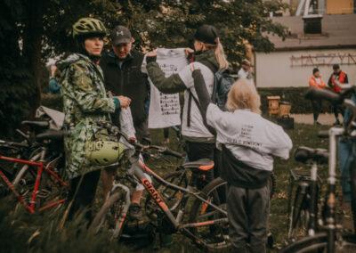Chłopiec zakładający koszulke rajdową, obok kobieta oglądająca koszulkę. Z lewej strony mężczyzna i kobieta. Wokół stoja rowery. Z tyłu napis maszynownia.