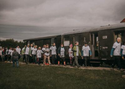 Ludzie idący gęsiego wzdłuż wagonów kolejki.