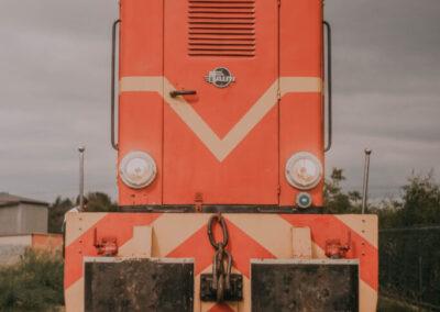 Czerwona lokomotywa kolejki wąskotorowej.