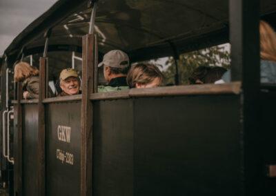 Mężczyźni w czapkach z daszkiem siedzą w pociągu, kobieta za nimi wygląda prze okno.