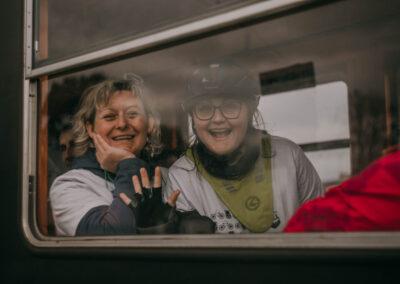 Dwie rozesmiane kobiety w oknie pociągu.