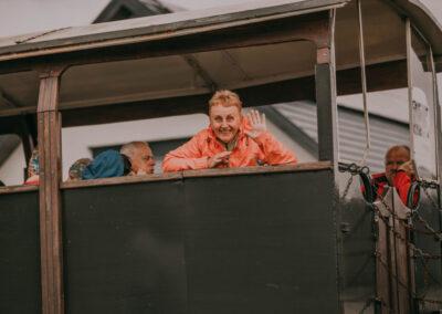 Kobieta w czerwonej kurtce stoi patrzy przez okno kolejki i macha. W wagonie siedzą inni pasażerowie.
