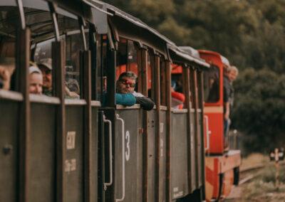 Ludzie wyglądający przez okna kolejki. W lokomotywie stoi mężczyzna.