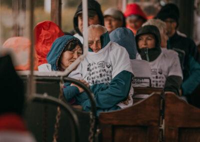 Ludzie w koszulkach rajdowych opatuleni w kurtki i kaptury siedzą w wagonie kolejki.