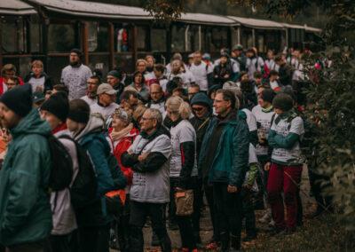 Duża grupa uczestników rajdu stojąca przy wagonach podstawionej kolejki.