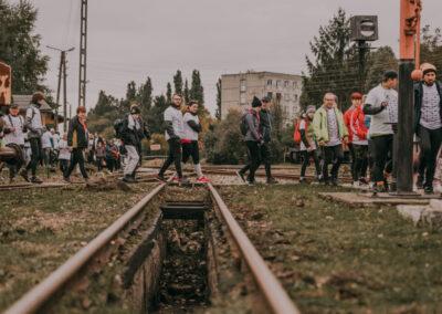 Uczestnicy rajdu idący jeden za drugim przez torowiskiw kierunku parowozowni.